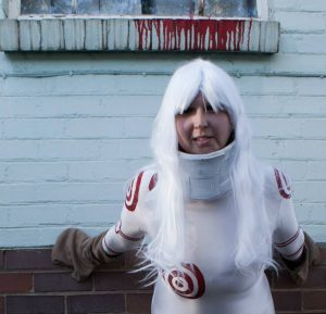 shiro cosplay standing by white wall with blood dripping behind - johannesburg