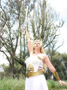 She-ra cosplay by Sam Secrets Johannesburg, South Africa. She-ra's sword is held above her head.