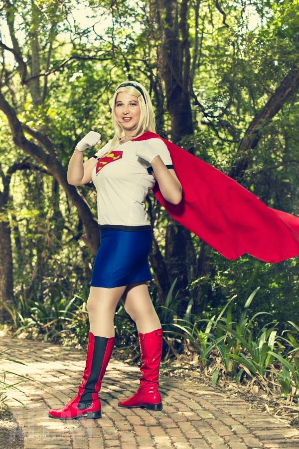 supergirl cosplay standing in park with cape flying