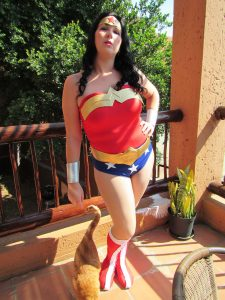 wonder woman cosplay standing on a balcony with a cat walking past