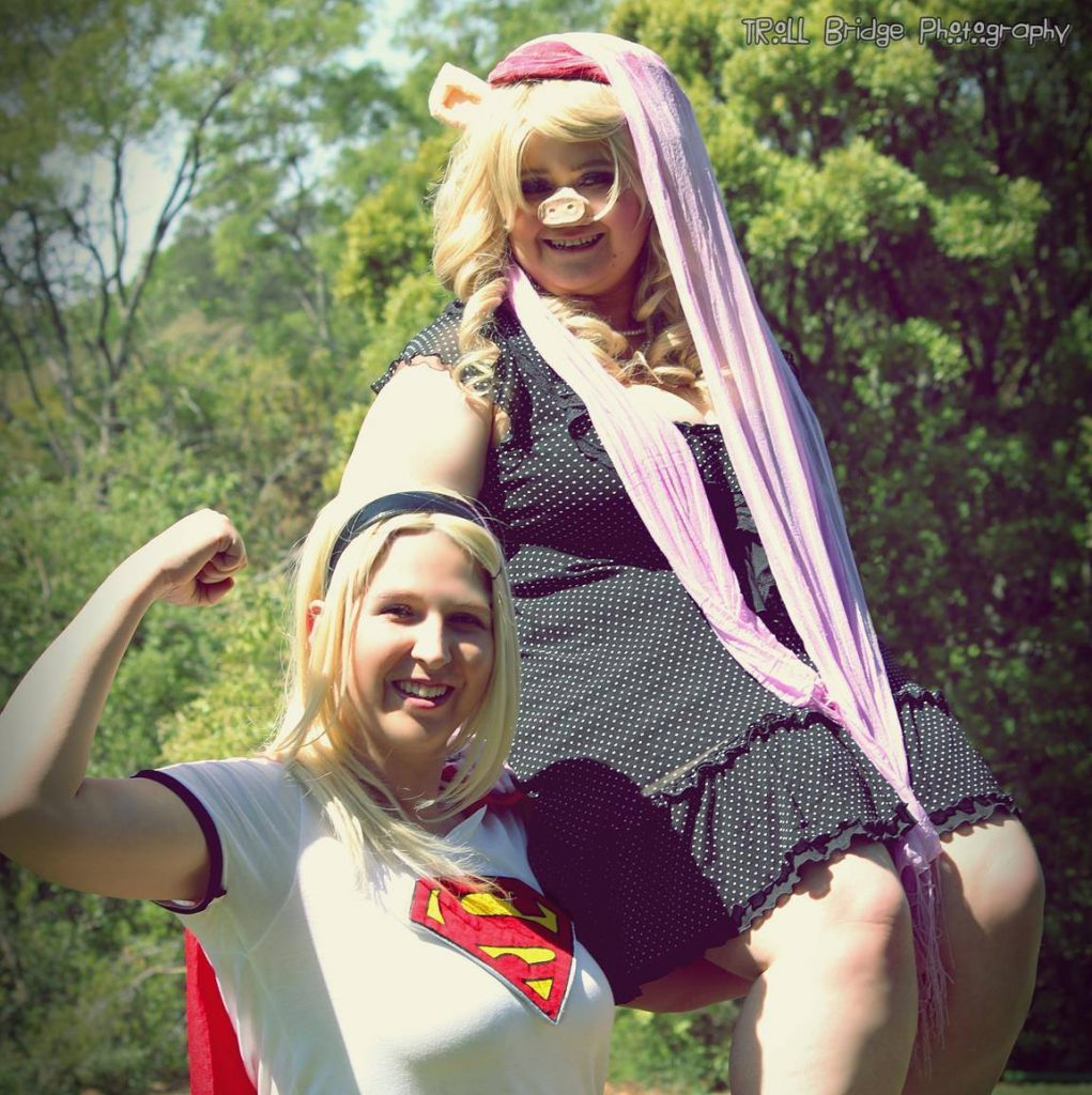 Supergirl cosplay holding up on her shoulder a Miss Piggy cosplay